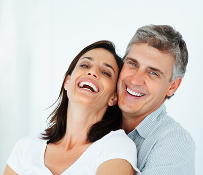 woman laughs while her husband hugs her from behind smiling in front of a white background