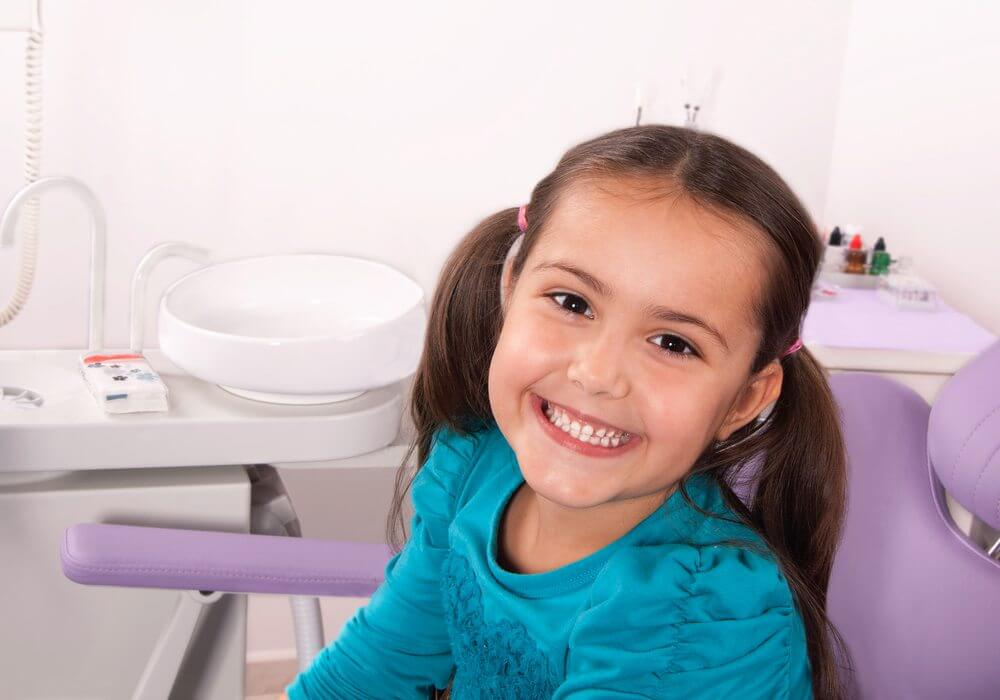 A young girl with pigtails smiling during her pediatric dentistry appointment